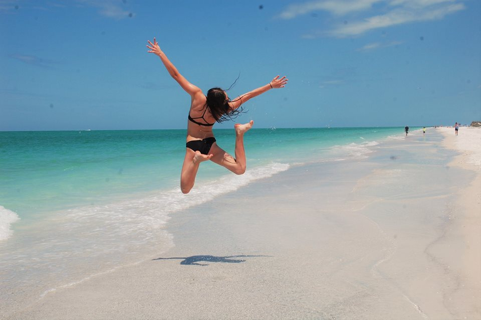 girl jumping up in the air on the beach
