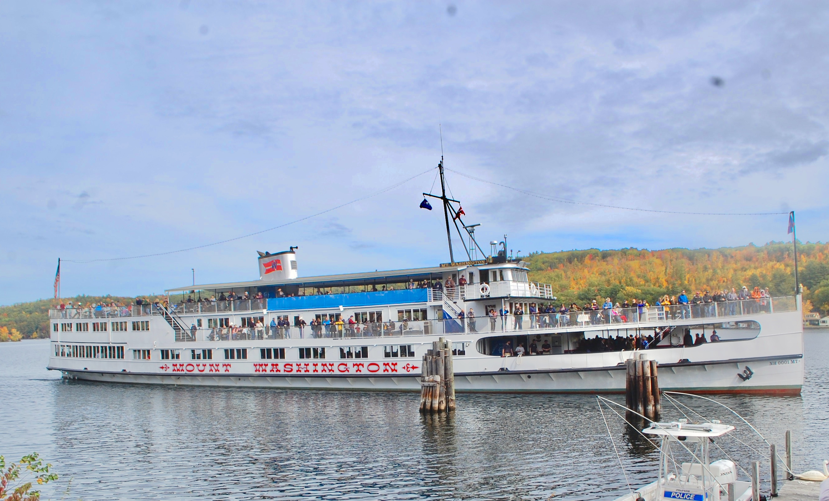 Mount Washington cruise ship with people on board and beautiful foliage in the background