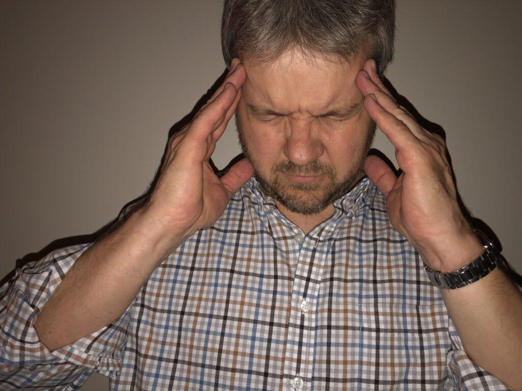 man holding his head with a headache