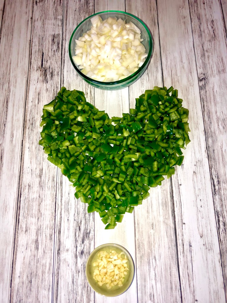 chopped onion in a bowl, chopped peppers shaped into a heart, small bowl of minced garlic