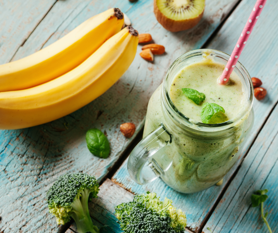 mason jar mug filled with a green smoothie, polka dotted straw with banana, almonds, broccoli, and kiwi surrounding it on teal wooden backdrop