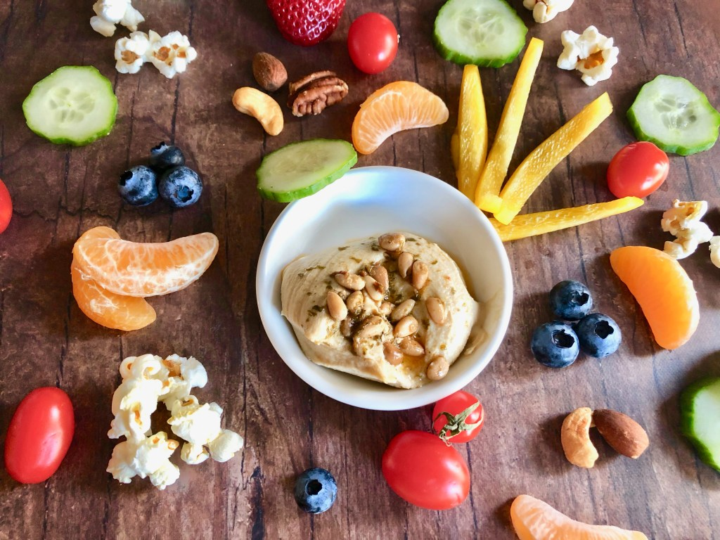 small bowl of hummus surrounded by colorful fresh fruit, vegetables, nuts, and pieces of popcorn