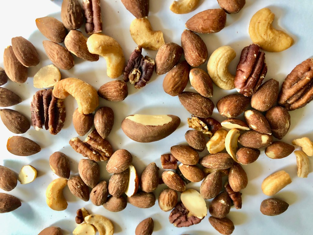 a single Brazil nut surrounded by numerous almonds, cashews, and pecans