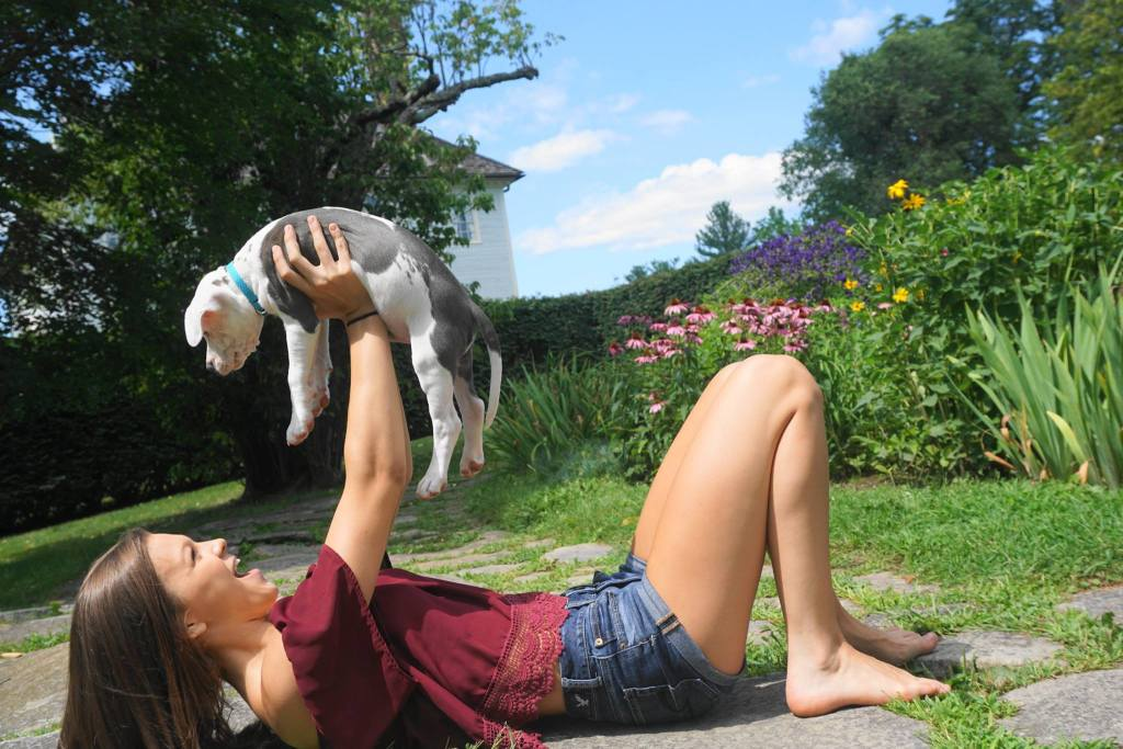 Teenaged girl lying on ground smiling holding up white and gray puppy