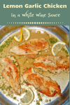 4 browned chicken breasts in skillet with sauce garnished with fresh thyme and lemon