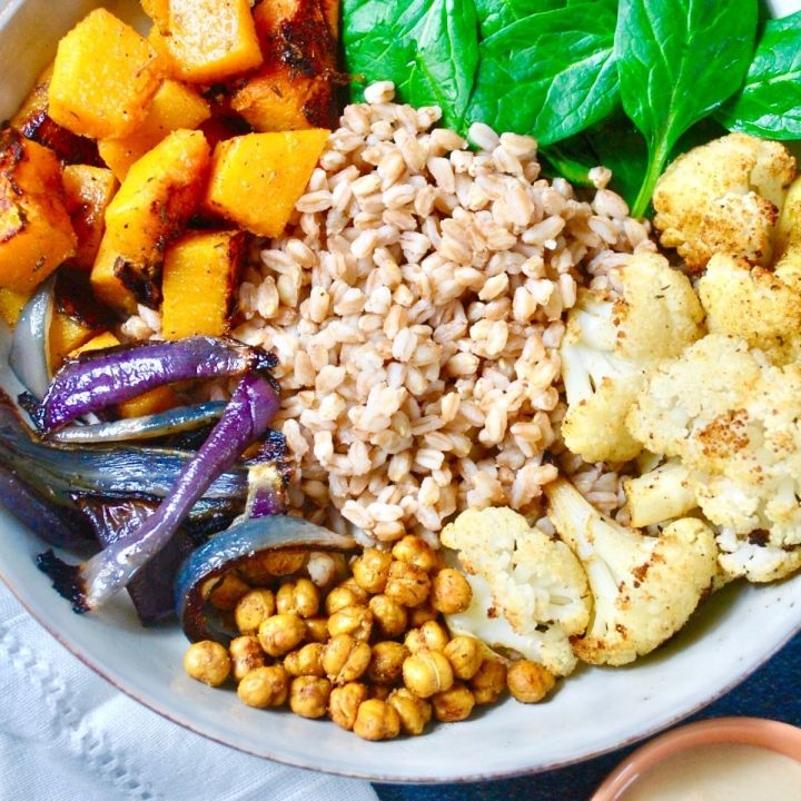 bowl of roasted cauliflower, butternut squash, red onion, spinach, toasted chickpeas and tahini dressing