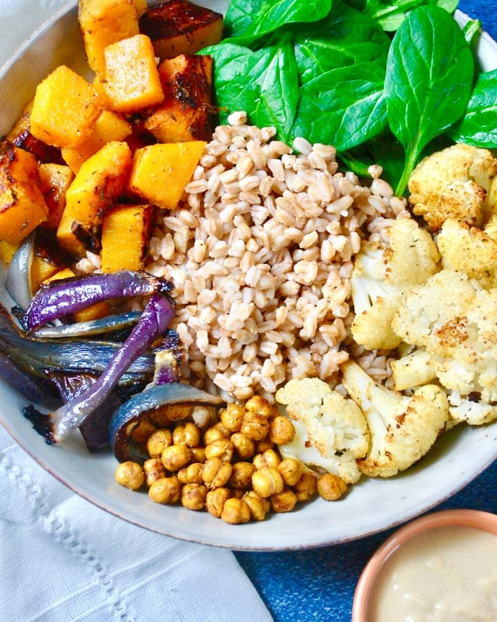 Bowl of roasted cauliflower, butternut squash, red onion, fresh spinach, toasted chickpeas and tahini dressing