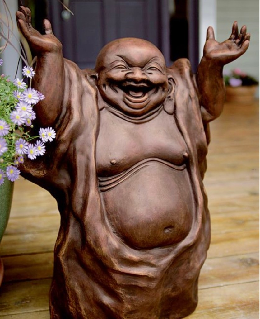 A wooden statue of a smiling buddha with his hands in the air