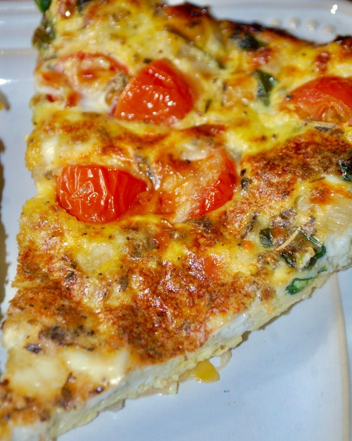 A slice of spinach, tomato & cheese frittata served on a white dish