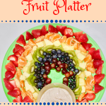 Red strawberries, Orange orange slices, Yellow pineapple, Green kiwi, Blue blueberries, and Purple grapes arranged to look like a rainbow on green platter with gold colored bowl full of dip