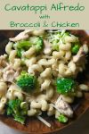 brown bowl filled with cheesy spiral pasta with broccoli and chicken