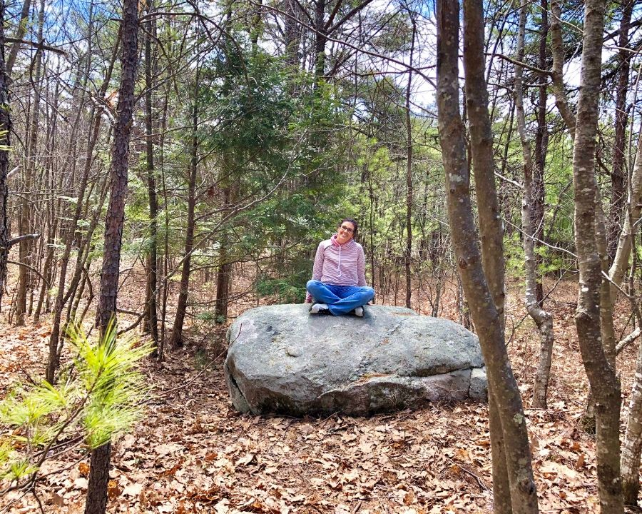 woman sitting cross legged on a rock in the woods