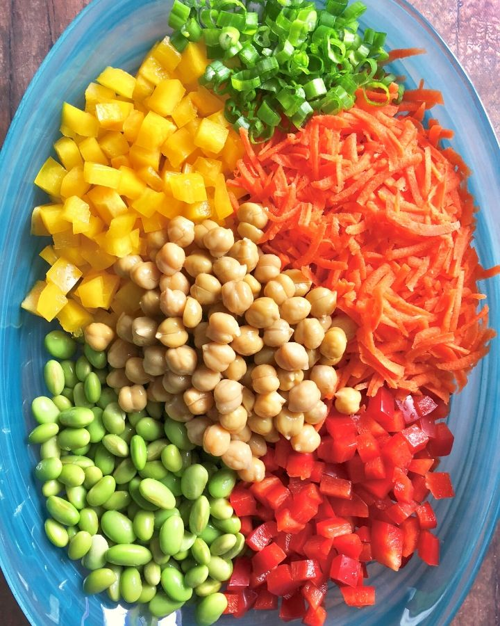 blue glass bowl with scallions, grated carrot, red diced bell pepper, yellow diced bell pepper, edemame, and chickpeas.