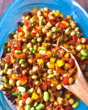 Blue glass bowl full of chickpeas, peppers, edamame, cranberries, carrots, etc.