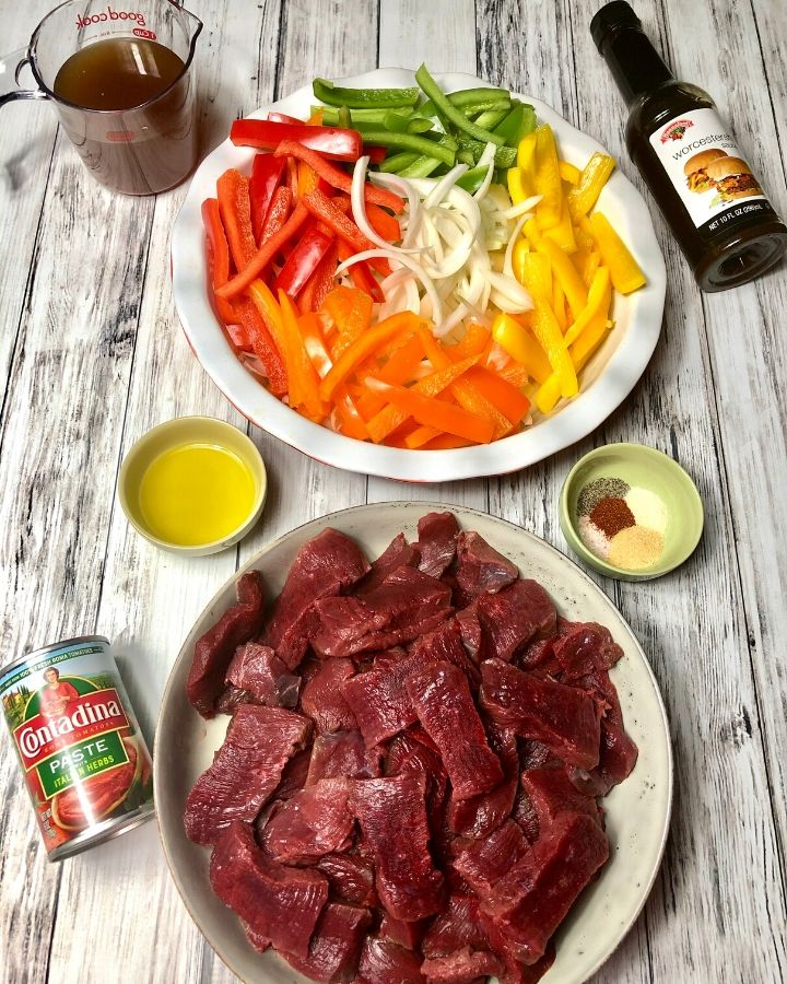 Plate of sliced, raw venison meat, sliced red, orange, yellow and green pepper, onion, beef broth, Worcestershire sauce, spices, olive oil, tomato paste,