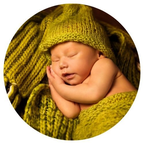 newborn sleeping with hands under his face with greenish yellow crocheted hat and blanket