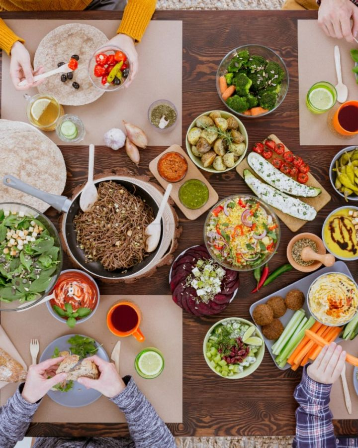 Four people eating around a table full of healthy food