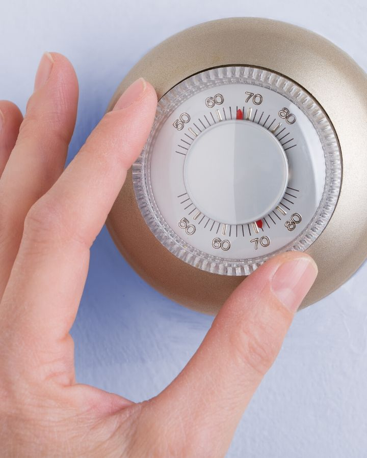 a hand turning down the temperature on a thermostat