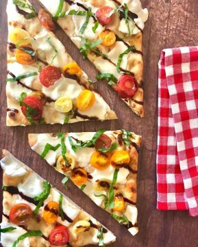flatbread pizza with melted mozzarella, basil, drizzled with balsamic glaze with a red and white plaid napkin