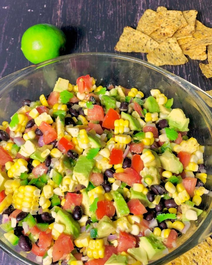 bowl of fiesta corn and avocado salad with tortilla chips and lime to the side