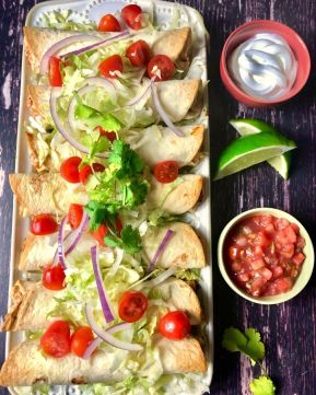 A platter full of flautas garnished with tomato, red onion, cilantro, salsa, sour cream, and lime wedges