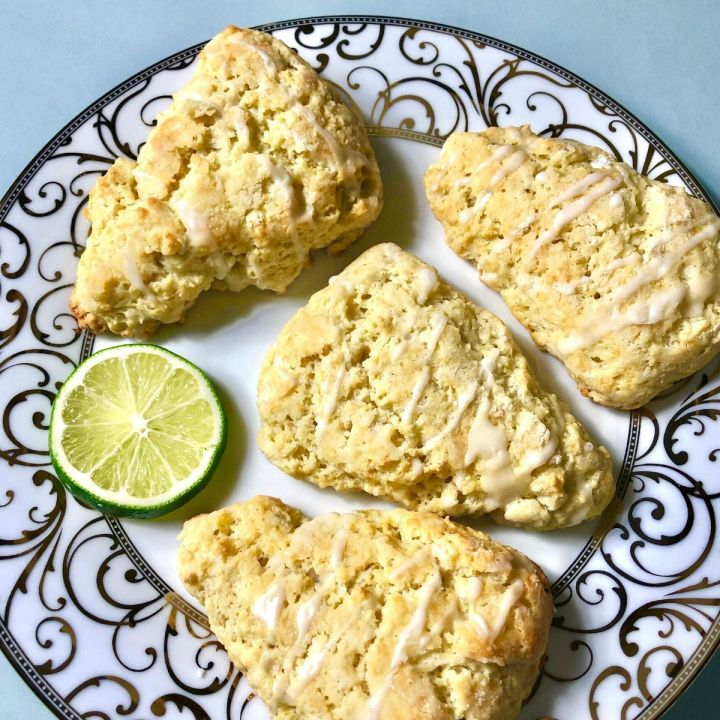four glazed scones on an elegant plate garnished with a piece of lime