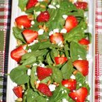 plate full of fresh spinach, sliced strawberries, goat cheese, and toasted pine nuts