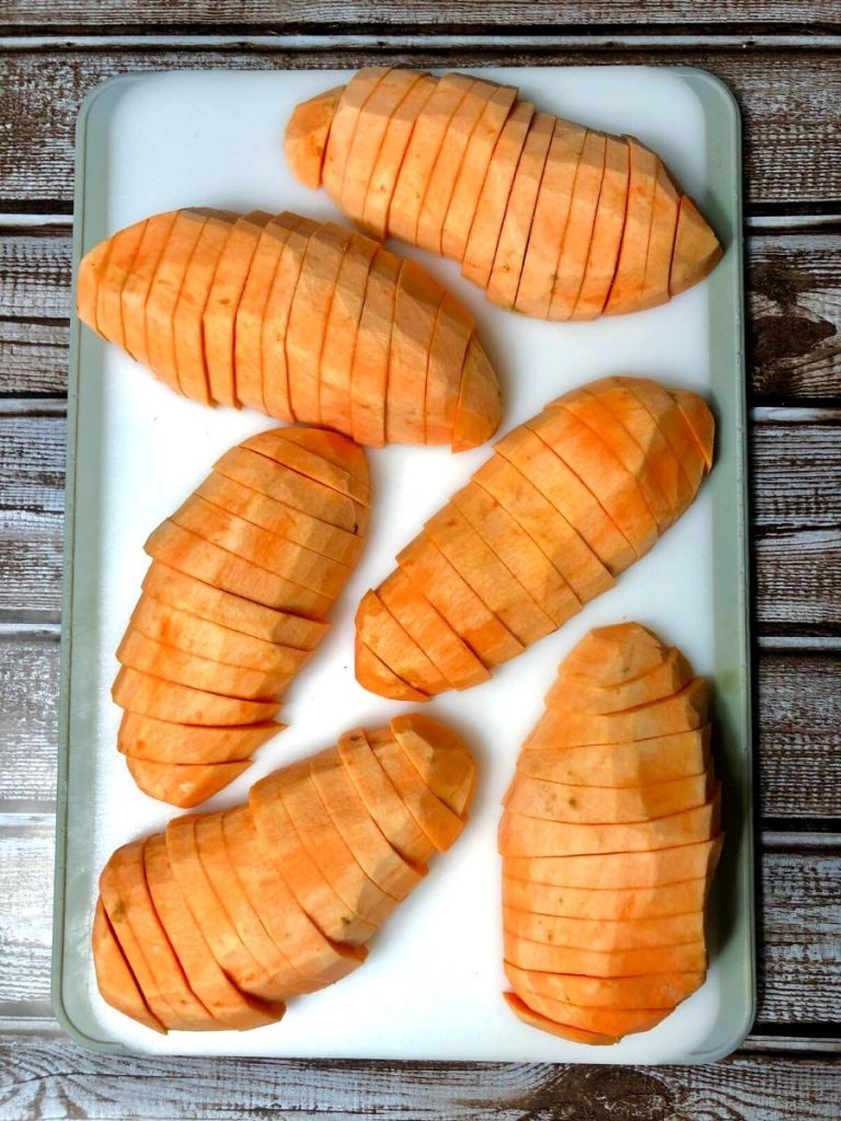 3 sweet potatoes sliced lengthwise in half and then sliced on a white cutting board