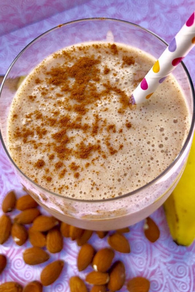 A smoothie in a glass with a pink, yellow, and purple polka dot straw; almonds and banana beside glass