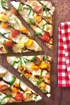 4 wedges of caprese pizza on brown table with red and white checkered napkin to the side