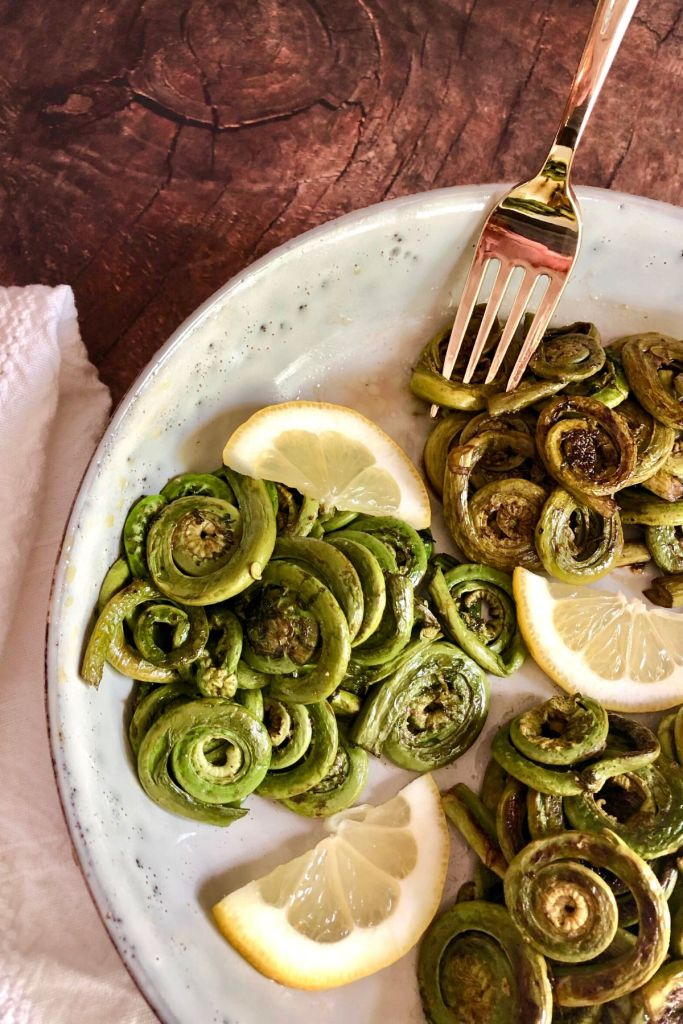 Cooked fiddleheads in a plate garnished with lemon wedges, gold fork, white napkin on side on brown table