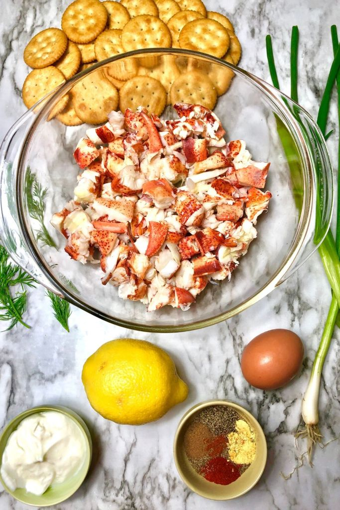 bowl of lobster meat surrounded by mound of crackers, green onion, dill, lemon, egg, yogurt, small dish of spices