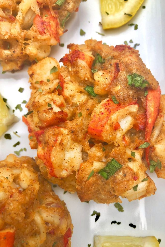 golden brown lobster cake garnished with lemon and parsley
