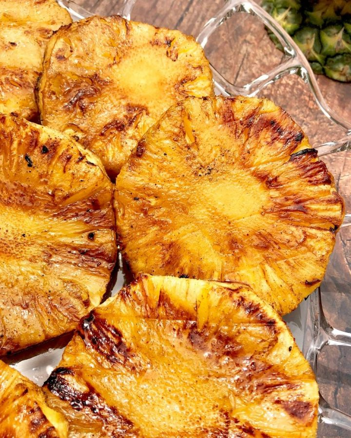 Grilled pineapple slices on a glass platter with a pineapple top in the upper right hand corner