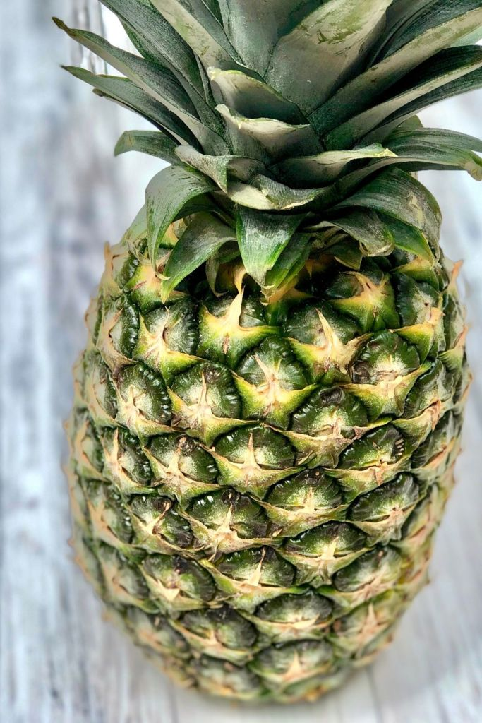 A fresh pineapple stood upright on a white wooden table