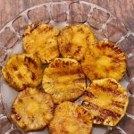 Eight grilled pineapple slices on a glass platter on a wooden table