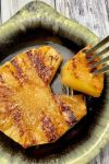 Grilled pineapple slice in ceramic bowl with fork