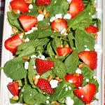 white rectangular place full of strawberry spinach salad on top of red plaid tablecloth