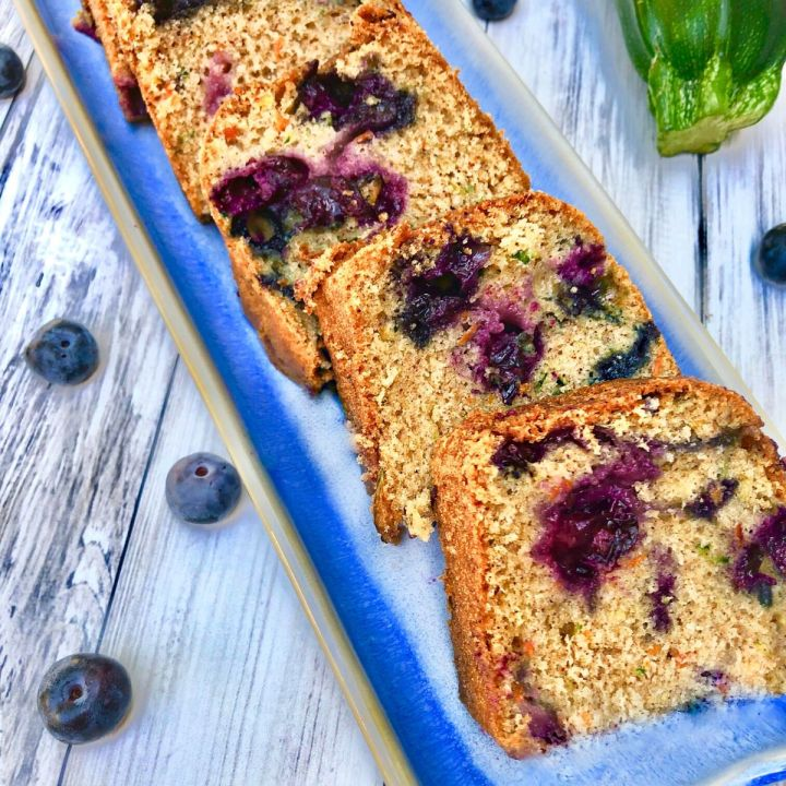 a narrow blue ceramic dish holding small slices of blueberry zucchini bread