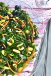 kale salad with blueberries, slivered almonds, shredded carrot, sliced green onion, and edemame