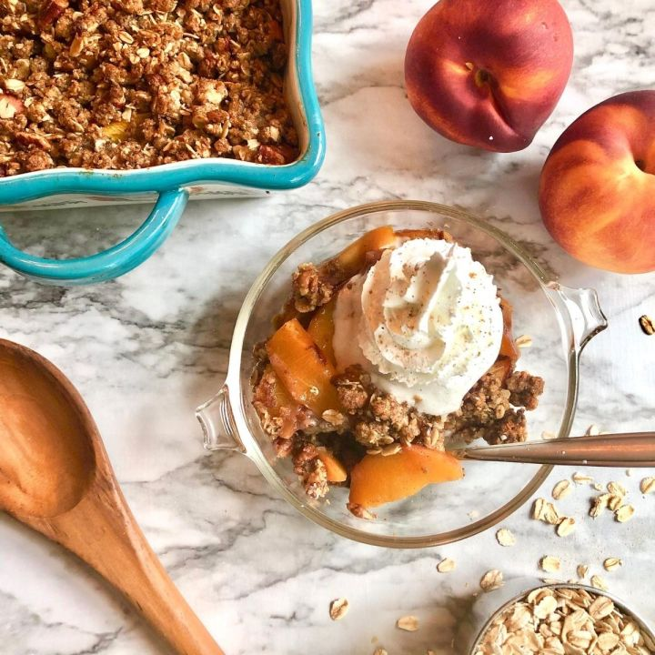 serving of peach crisp with a spoon surrounded by baking dish of peach crisp, 2 peaches, wooden spoon, and scattered oats