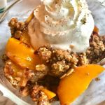 dish of peach crisp with oat topping and pecans garnished with whipped cream and sprinkled with cinnamon