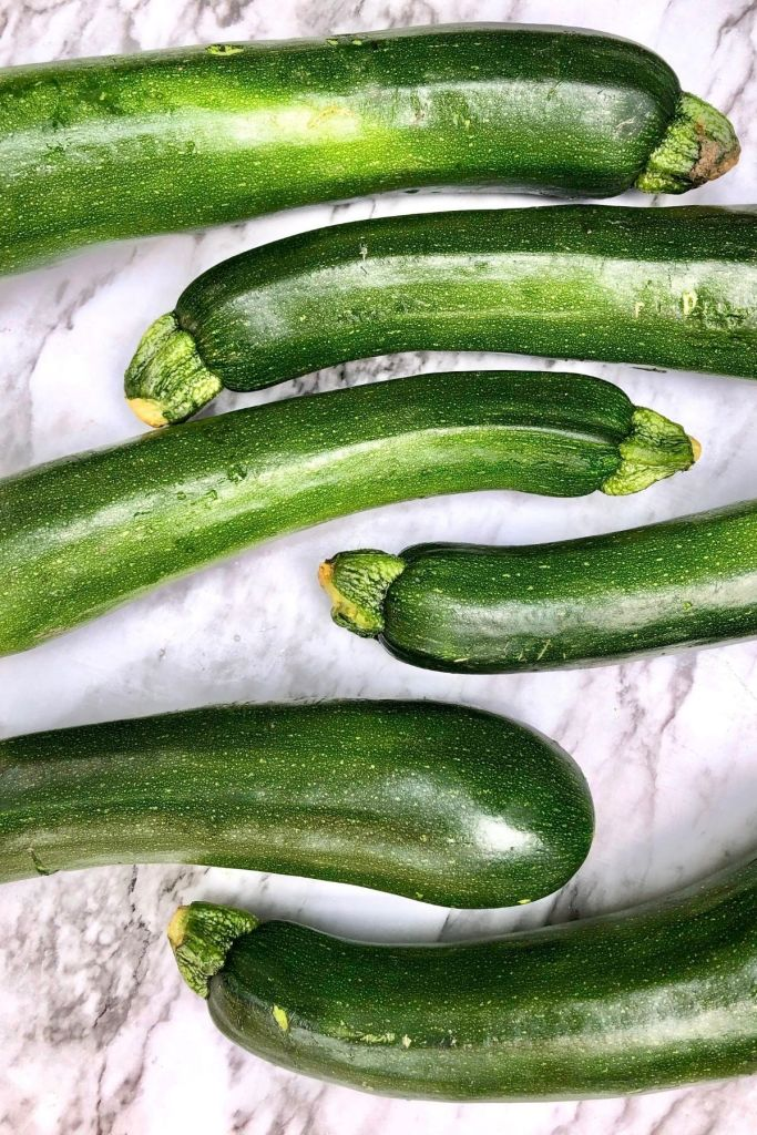 Five whole zucchini on white background