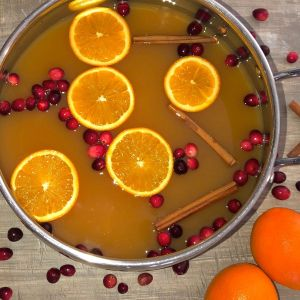 pot of mulled cider with cranberries, sliced oranges, and cinnamon sticks