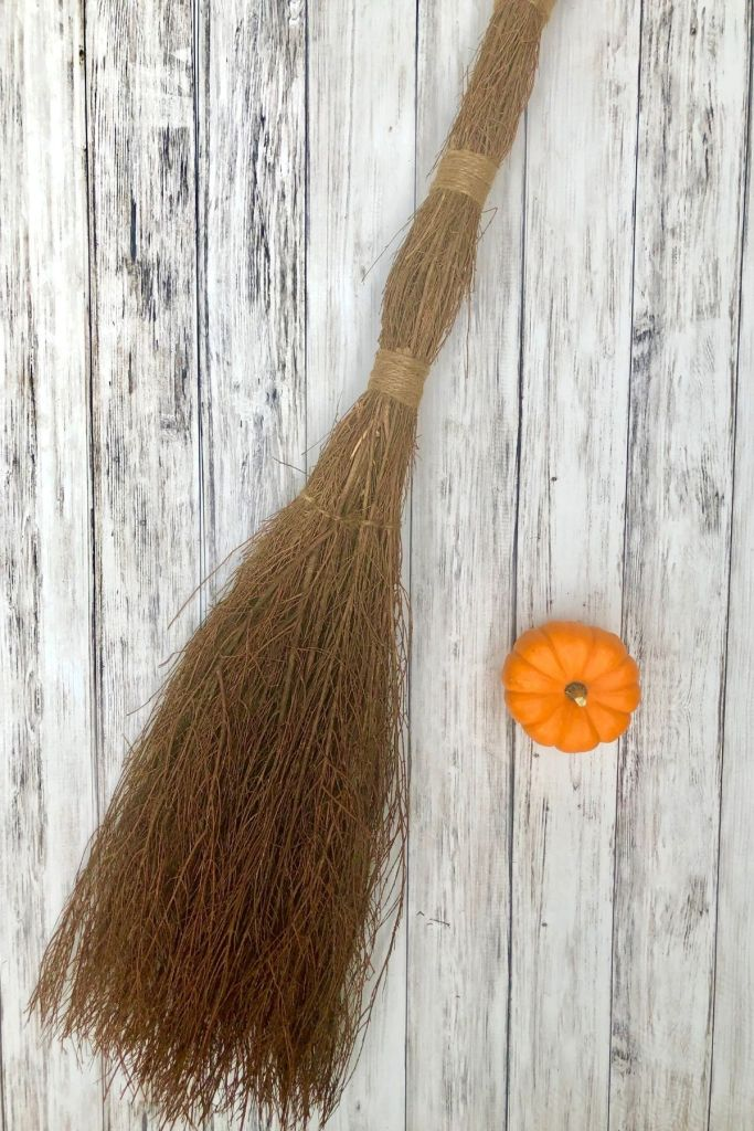 cinnamon broom with a small orange pumpkin