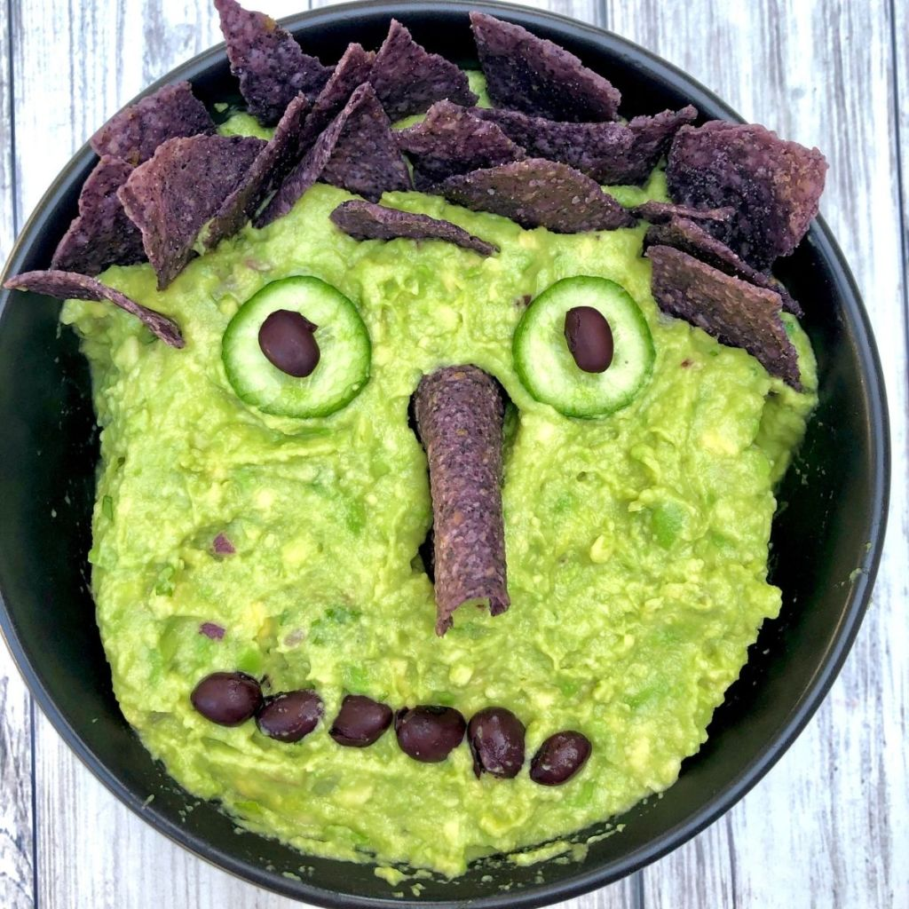 bowl of guacamole with black tortilla chips for hair, cucumber slices and black beans for eyes, tortilla chip for nose and black beans for mouth