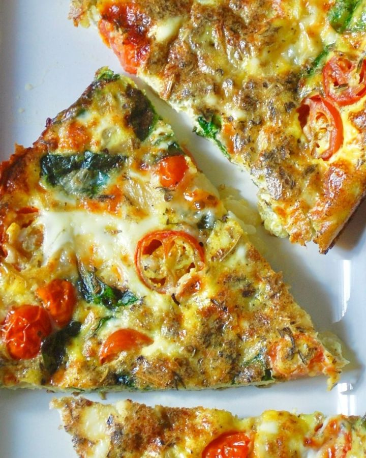 spinach tomato and cheese frittata slices on white dish