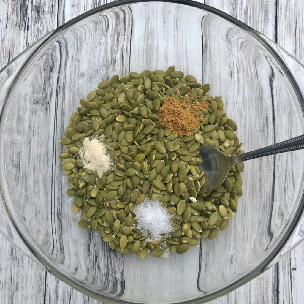a bowl of raw green pepitas with spices added and spoon