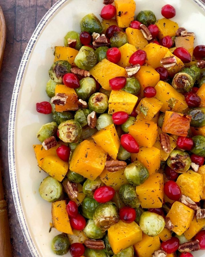 roasted butternut squash and Brussels sprouts with cranberries and pecans on a white oval plate with wooden spoon to the left
