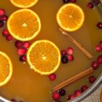 pot of hot wassail with orange slices, cranberries, and cinnamon sticks
